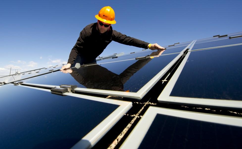 personne qui pose des panneaux solaires