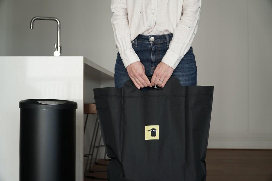 femme à côté d'une poubelle qui tient un sac