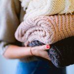 femme qui tient une pile de vêtements en laine