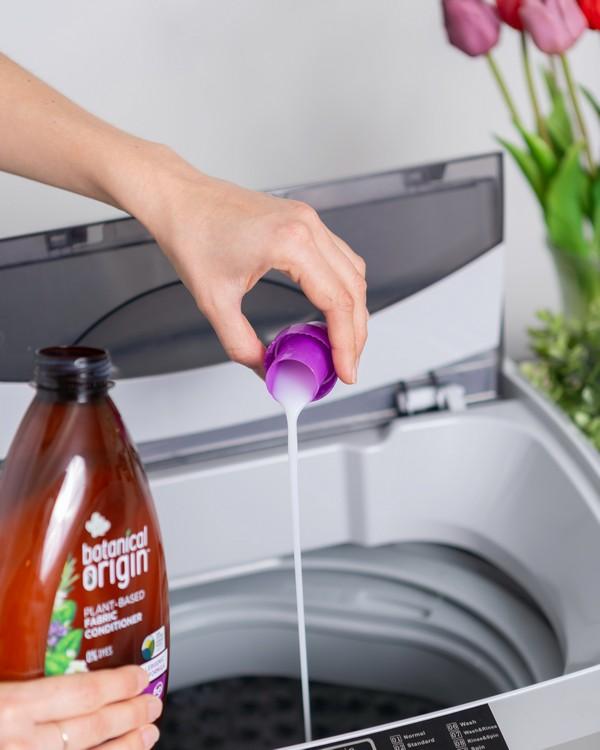 main d'une personne qui verse de la lessive dans une machine à laver