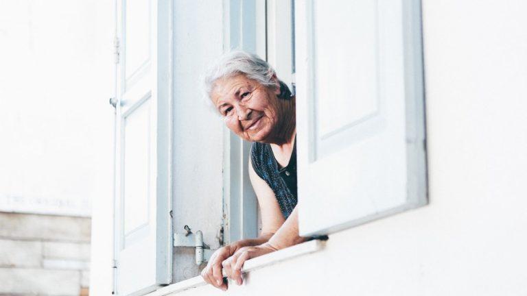 mamie qui regarde dans la rue depuis sa fenêtre