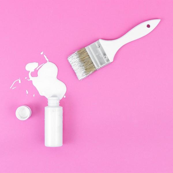 pinceau avec peinture blanche sur fond rose