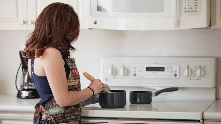 femme de dos qui cuisine sur sa cuisinière électrique
